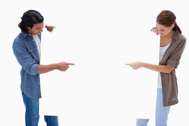 Couple à la recherche et en pointant à signe vierge dans leurs mains