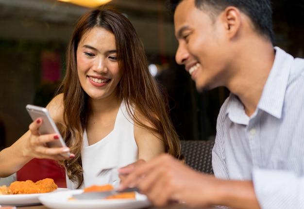 Couple à la recherche sur smartphone au magasin d'alimentation