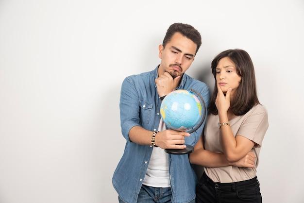 Couple réfléchi à la recherche sur une carte du globe.