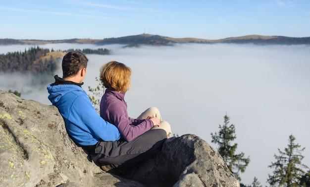 Couple regardant autour. le brouillard couvrait les collines