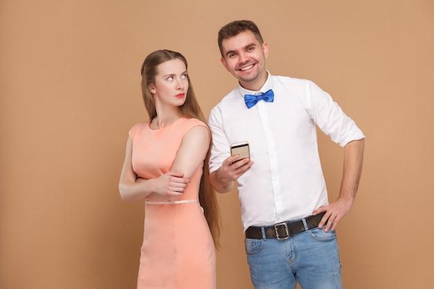 Couple regardant la caméra avec un sourire à pleines dents et une femme le regardant avec un visage malheureux