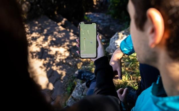 Couple regardant une carte numérique et un gps au milieu de la forêt