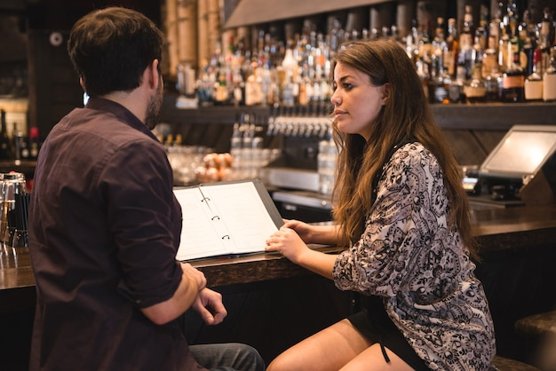 Couple regardant menu au comptoir du bar