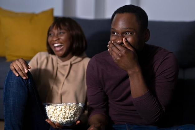 Couple regardant netflix ensemble à la maison à l'intérieur