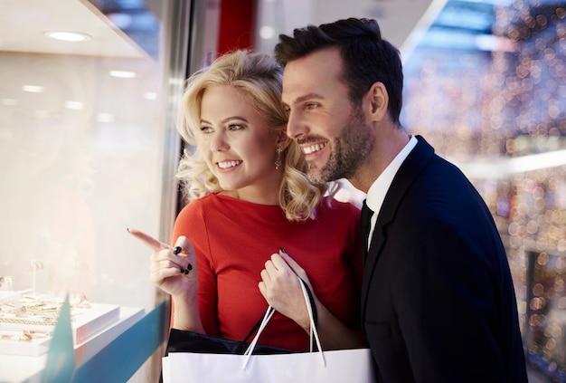 Couple regardant par la fenêtre des magasins
