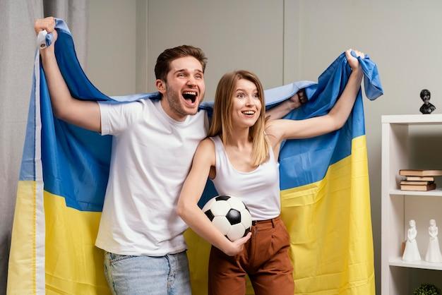 Couple regardant le programme de sport à la télévision