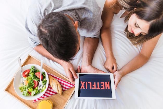 Couple regardant la série netflix près du plateau avec de la nourriture
