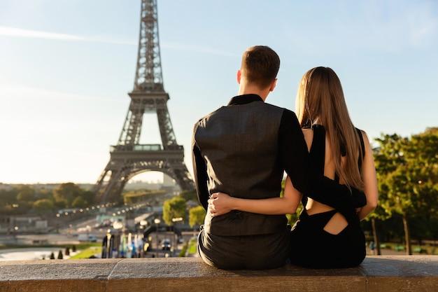 Couple regardant la tour eiffel, rendez-vous romantique à paris.