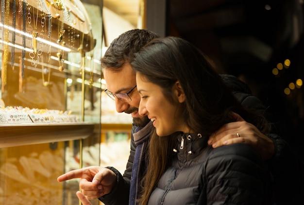 Couple regardant la vitrine d'un bijou en plein air.