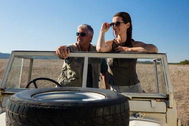 Couple, regarder loin, debout, dans, véhicule, sur, champ