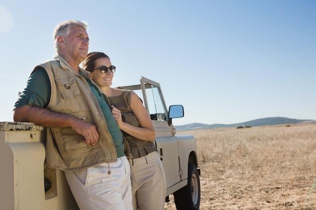 Couple, regarder loin, debout, véhicule, sur, champ