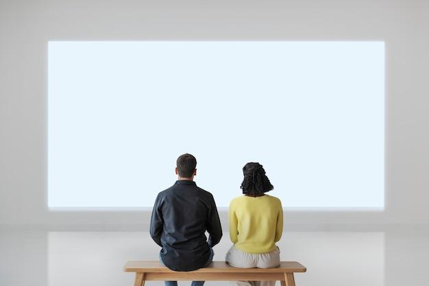 Couple, regarder, mur blanc, vue postérieure