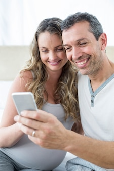 Couple, regarder, smartphone, chambre à coucher