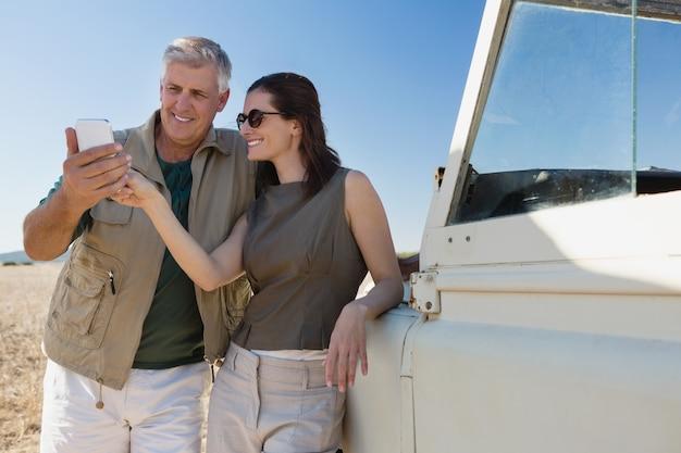 Couple, regarder, téléphone portable, par, véhicule