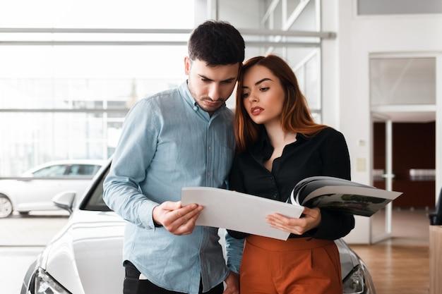 Couple, regarder, voiture, concessionnaire, journal