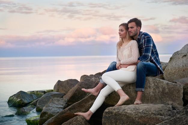 Couple relaxant sur les rochers