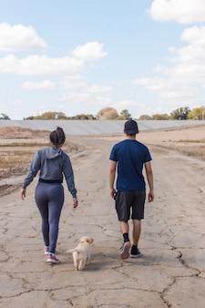 Couple de remise en forme avec le dos tourné marchant à côté de leur adorable chiot sur la plage.
