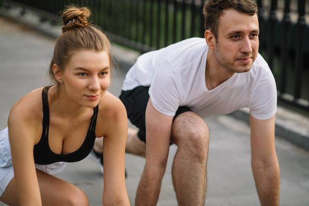Couple de remise en forme prêt à courir dans le parc extérieur, en ville