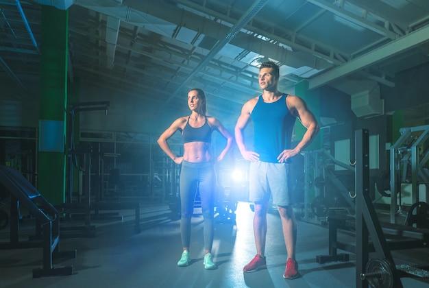 Le couple de remise en forme se tient dans la salle de sport sur le fond clair et lumineux