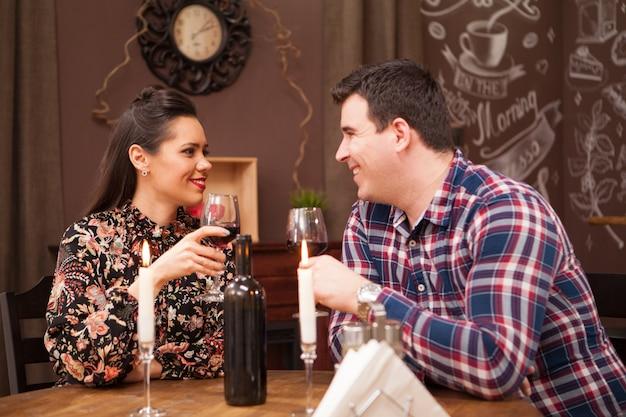 Couple à un rendez-vous assis dans un pub hipster buvant du vin rouge. fête .