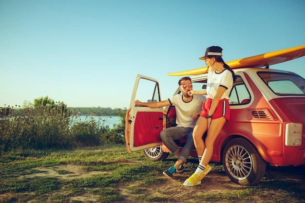 Couple reposant sur la plage un jour d'été près de la rivière