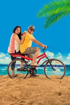Couple de retraités asiatiques indiens avec leur vélo ou leur vélo sur la plage, effet de mauvaise humeur