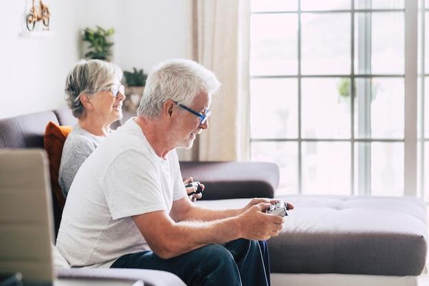 Couple de retraités caucasiens jouant à des jeux vidéo ensemble à la maison assis sur le canapé - femme mûre et homme mariés - deux se fiancent pour toujours - tenant un contrôleur ou un joystick