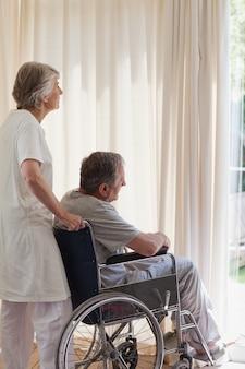 Couple de retraités regardant par la fenêtre