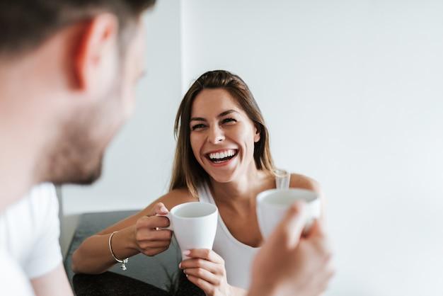Couple riant buvant du café le matin.