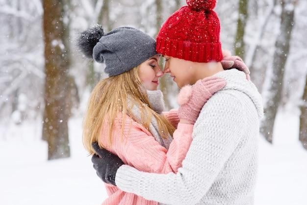 Couple romantique amoureux et câlins en plein air en hiver
