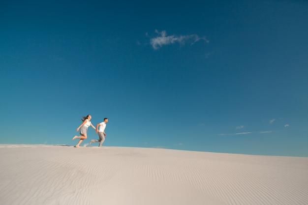 Couple romantique amoureux en cours d'exécution sur le sable blanc dans le désert