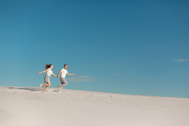Couple romantique amoureux en cours d'exécution sur le sable blanc dans le désert.