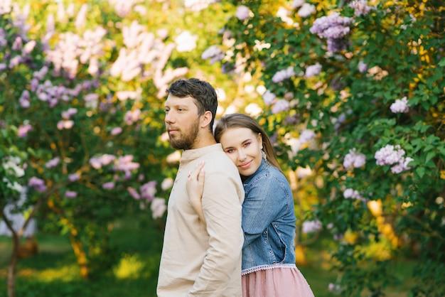 Couple romantique amoureux embrasse au printemps dans un jardin lilas en fleurs