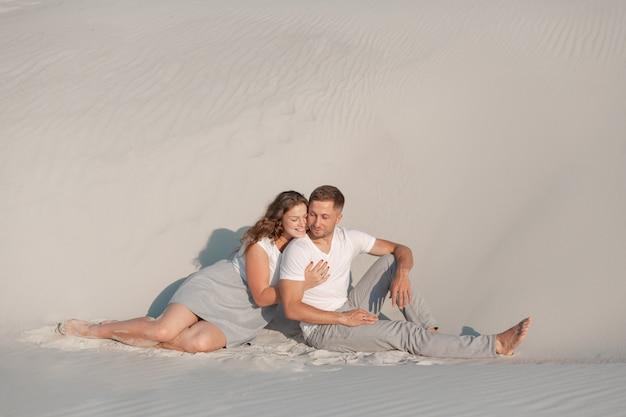 Couple romantique assis sur le sable blanc et huggins, dans le désert