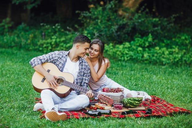 Couple romantique assis sur le tapis de la couverture dans le parc et jouer de la guitare.