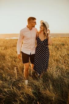 Couple romantique au chapeau marchant dans la prairie.
