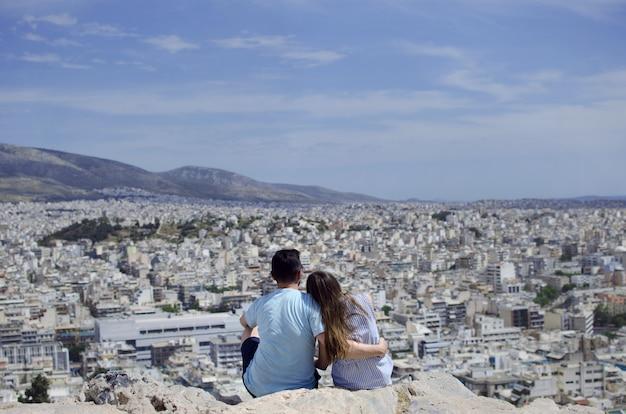Couple romantique au-dessus d'athènes depuis la montagne philosophique