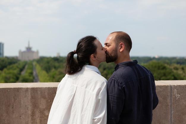 Couple romantique célébrant l'anniversaire de la relation s'embrassant sur la terrasse de la tour