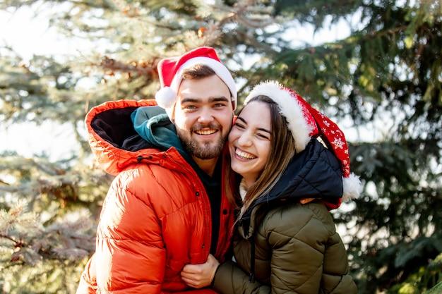 Couple romantique en chapeaux de noël près de sapin.