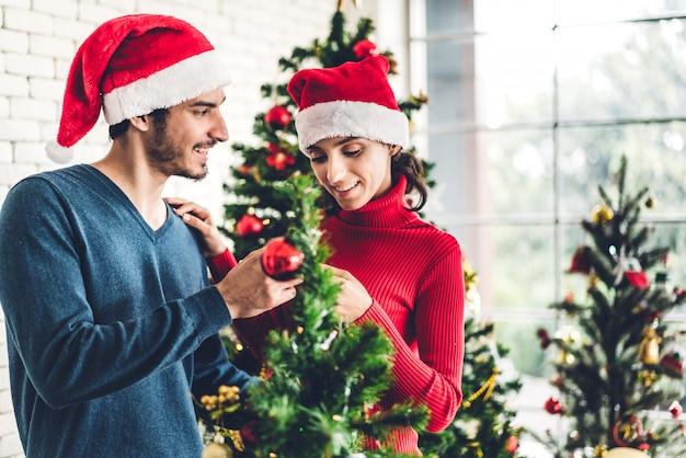 Couple romantique avec chapeaux de santa s'amusant à décorer un arbre de noël et souriant tout en célébrant le réveillon du nouvel an et en profitant du temps passé ensemble à la maison à noël