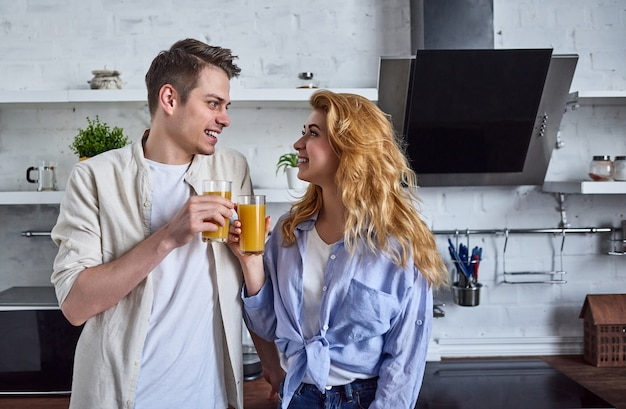 Couple romantique dans la cuisine de la maison. une belle femme et un homme séduisant passent un bon moment debout dans la cuisine et boivent du jus.