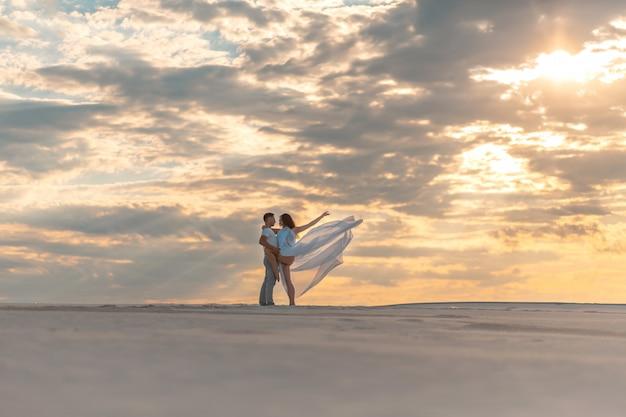 Couple romantique dansant dans le désert de sable au coucher du soleil