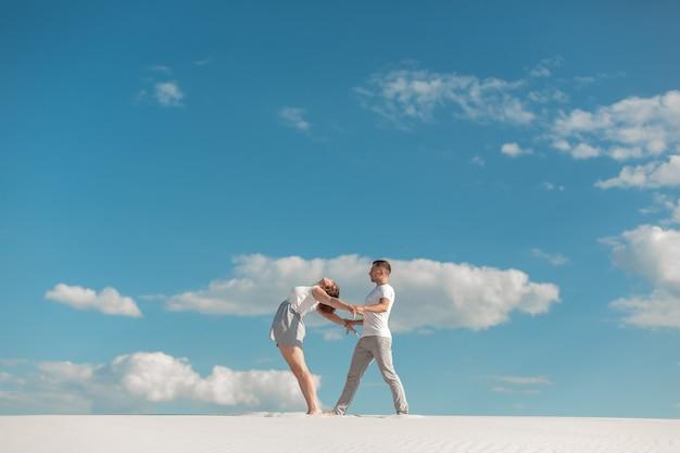 Couple romantique dansant dans le désert de sable sur fond de ciel bleu.