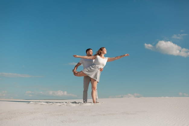 Couple romantique dansant dans le désert de sable à la scène de ciel bleu