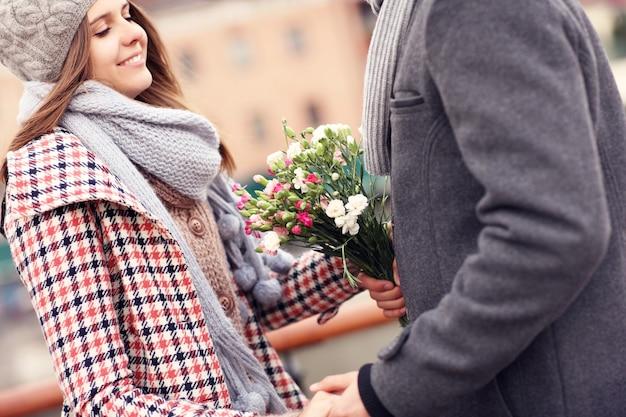 Un couple romantique à une date tenant des fleurs