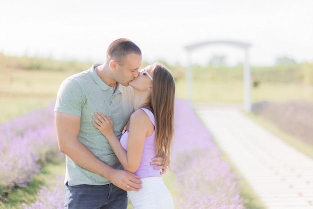 Couple romantique debout en plein air, s'embrassant.