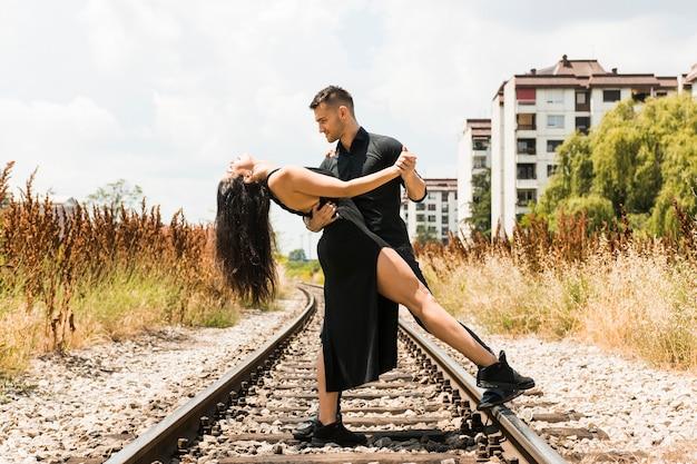 Couple romantique élégant tangoing sur la voie ferrée