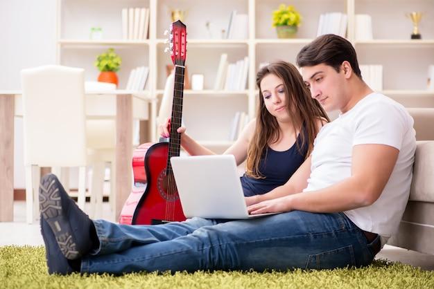 Couple romantique jouant de la guitare au sol