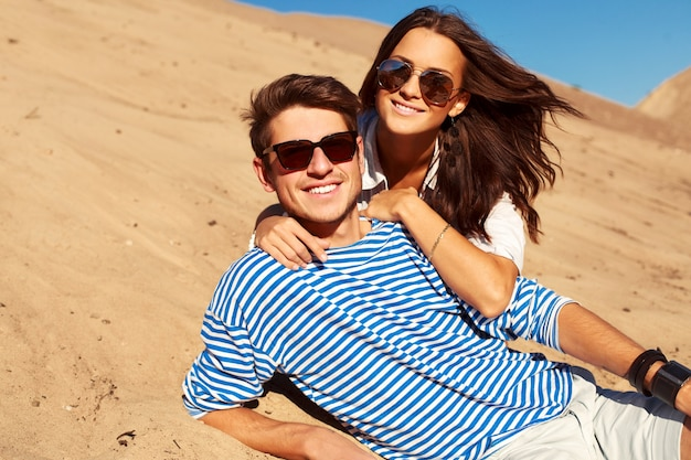 Couple romantique avec des lunettes de soleil couché sur le sable