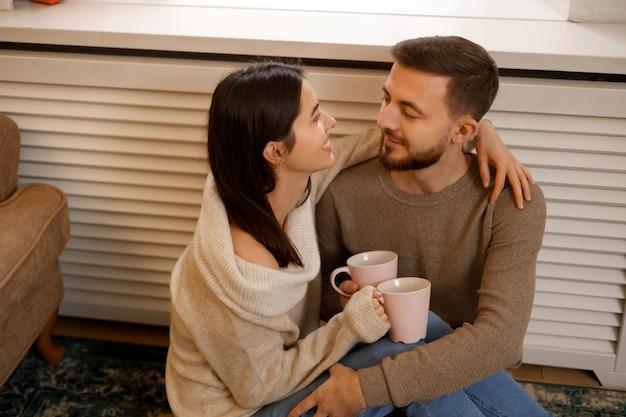 Couple romantique à la maison. une jolie jeune femme et bel homme apprécient de passer du temps